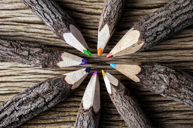 Концепция совместной работы цветного карандаша на фоне дерева