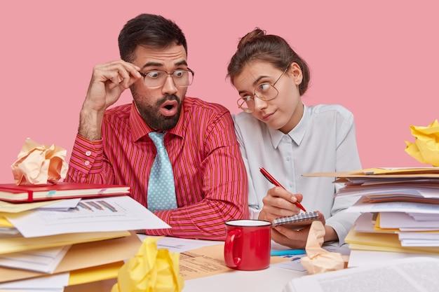 チームワークの概念。大きな眼鏡をかけた若い同僚が一緒にブレインストーミングし、将来の商取引のためにドキュメントを研究し、スパイラルメモ帳にメモを書き留めます