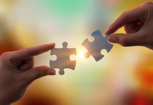 Концепция совместной работы, сотрудничества и партнерства, человеческие руки, держащие кусочки головоломки