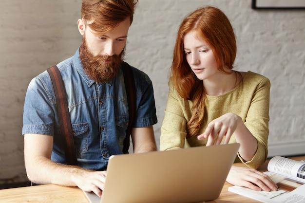 Concetto di lavoro di squadra e cooperazione. due studenti che lavorano insieme su un progetto comune utilizzando il computer portatile.