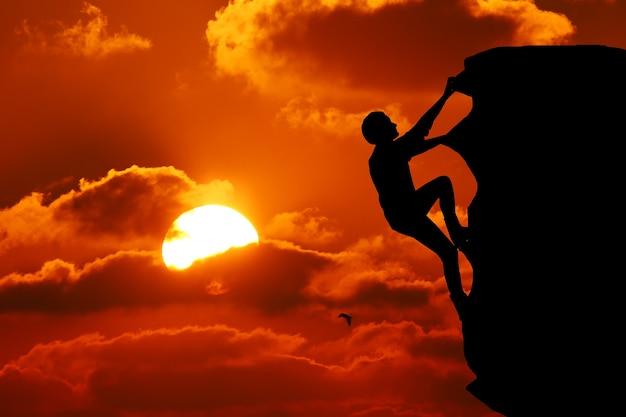 チームワークのカップルのハイキングは、山、日没でお互いの信頼の支援シルエットを助けます。登山チームの上で助け合う男女ハイカーのチームワーク