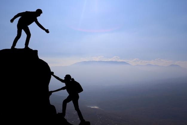 팀워크 커플 하이킹은 산, 일몰에서 서로 신뢰 지원 실루엣을 돕습니다. 등산 팀 위에서 서로 돕는 남녀 등산객의 팀워크