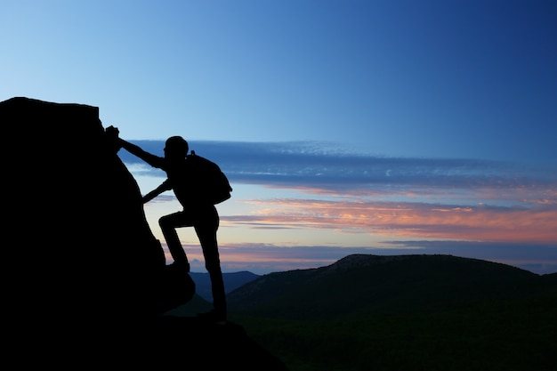 Teamwork couple hiking help each other trust assistance silhouette in mountains, sunset. teamwork of man and woman hiker helping each other on top of mountain climbing team