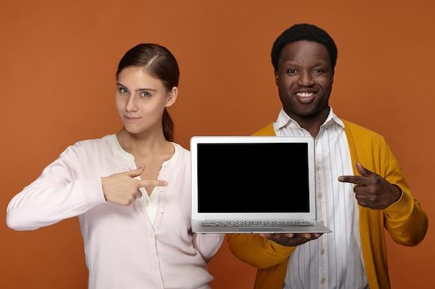 Lavoro di squadra, gadget elettronici e concetto di occupazione. felice fiducioso giovane femmina europea e positivo elegante maschio dalla pelle scura che punta le dita anteriori allo schermo del computer portatile copyspace vuoto e sorridente