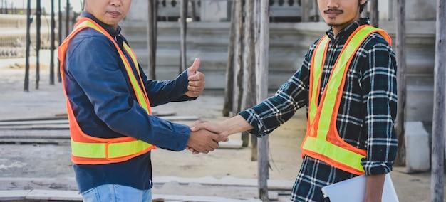 Работа в команде инженер пожать руку на фоне строительства сайта
