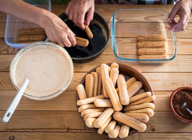 甘いイタリアンケーキ、ティラミスを準備するキッチンの人々のためのチームワーク。木製のテーブルのすべての材料。窓からの明るい光