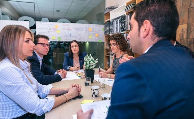 本社のテーブルに座ってビジネス戦略についての会議を持っているチームワーク
