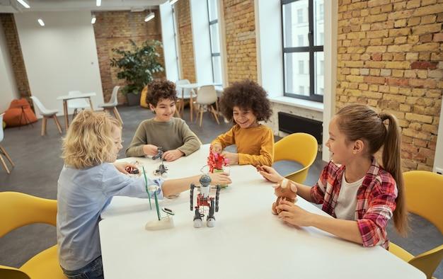 테크니컬한 장난감을 가지고 노는 동안 즐거운 시간을 보내는 활기찬 다양한 아이들의 팀워크