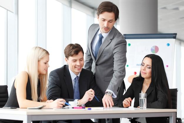 オフィスでレポートを議論するビジネスマンのチームワーク