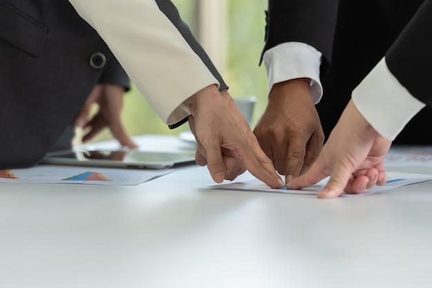 Совместная работа деловых людей пальцем к цели вместе на собрании.