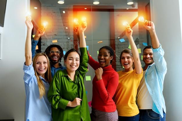ビジネスパーソンのチームワークは、照らされた電球を保持します