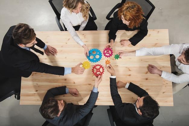 기업인의 팀워크는 함께 작동하고 기어 조각을 결합합니다. 파트너십 및 통합 개념