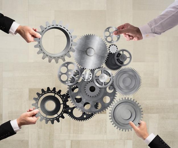 ビジネスマンのチームワークが協力して、歯車を機械システムに結合します