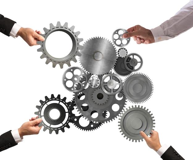 Командная работа бизнесменов, работающих вместе, объединяет части шестерен в механическую систему.