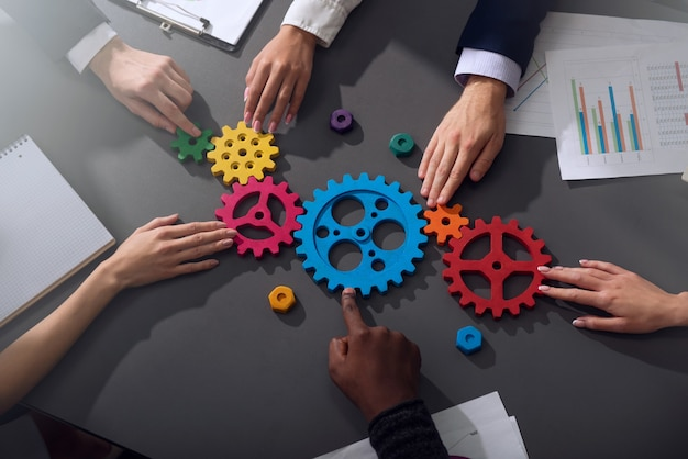 기업인의 팀워크가 함께 작동하고 기어 조각을 결합합니다.