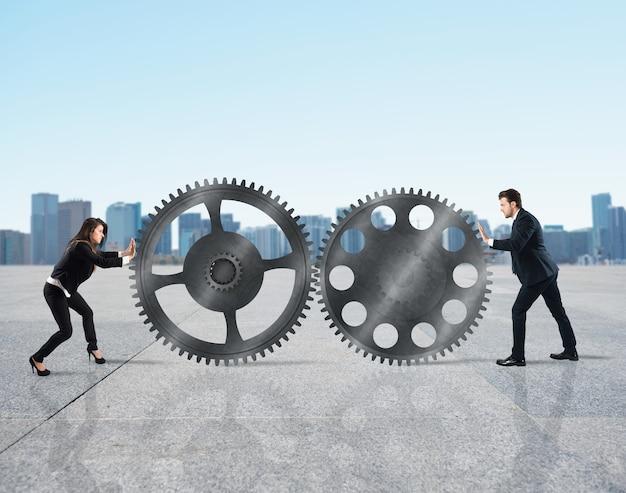 Командная работа бизнесменов работает вместе по системе шестеренок.