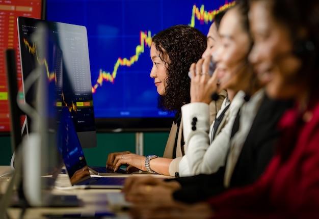 행복한 여성 거래 마케팅 운영자의 팀워크는 마이크 헤드셋을 착용하고 사무실에 있는 차트 그래프 모니터에서 비트코인 암호화폐 증권 거래소에서 거래 거래를 구매하도록 하며 웃고 있습니다.
