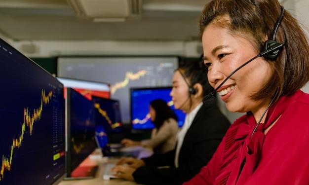 행복한 여성 거래 마케팅 운영자의 팀워크는 마이크 헤드셋을 착용하고 앉아 웃고 있다