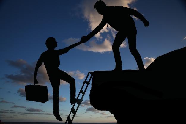 Работа в команде двух мужчин, помогающих друг другу на вершине горы, профессиональная команда альпинистов