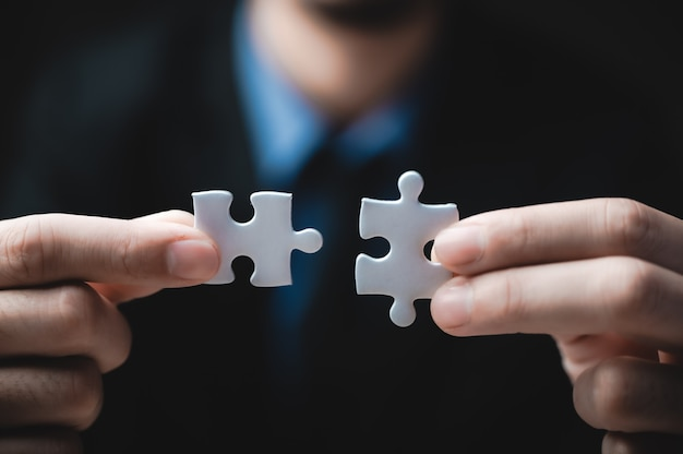 Teamwork of partners, concept of integration and startup with puzzle pieces