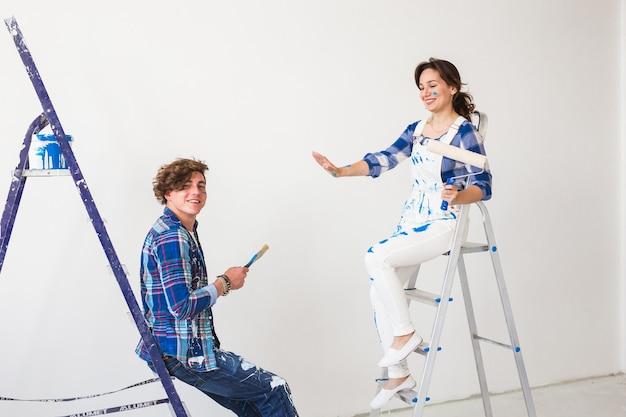 Коллективная работа по ремонту и ремонту концепции мужчина и женщина, покрытые краской, сидя на лестницах