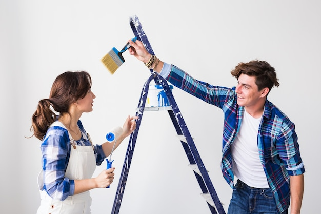 チームワーク、リノベーション、修理のコンセプト – アパートで模様替えをするおかしなカップルのポートレート。