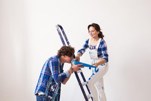 Работа в команде, ремонт и концепция ремонта - портрет забавной пары, делающей косметический ремонт в квартире.
