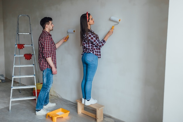 Teamwork and repair concept - young couple with cat doing a renovation in new apartment