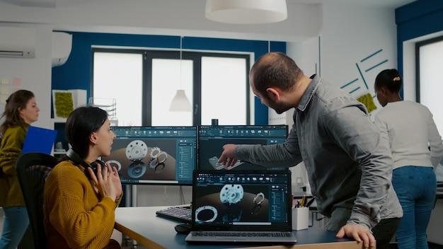 Совместная работа по обмену идеями о промышленном проекте по анализу трехмерных шестерен, глядя на компьютер с помощью программного обеспечения сапр, сопоставляемого с моделью с ноутбука Premium Фотографии