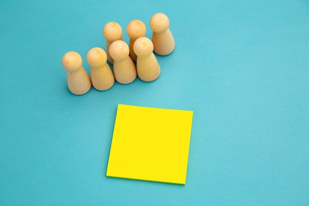 Teamwork, teambuilding mockup, company structure. wooden figures stands near yellow sticky note, place for text