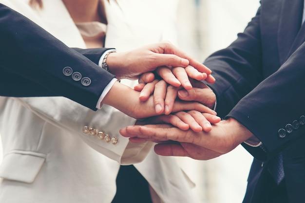 チームワーク一緒にコンセプト。タッグチームの力に挨拶するハイタッチの多様性の人々のグループ。多民族の人々は一緒に働くグループです。ビジネスチームの成功におけるボランティアのコラボレーション