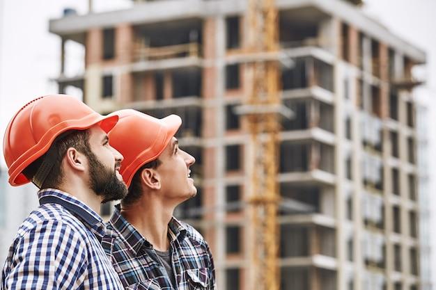 Работа в команде два молодых и веселых строителя в красных касках смотрят и работают