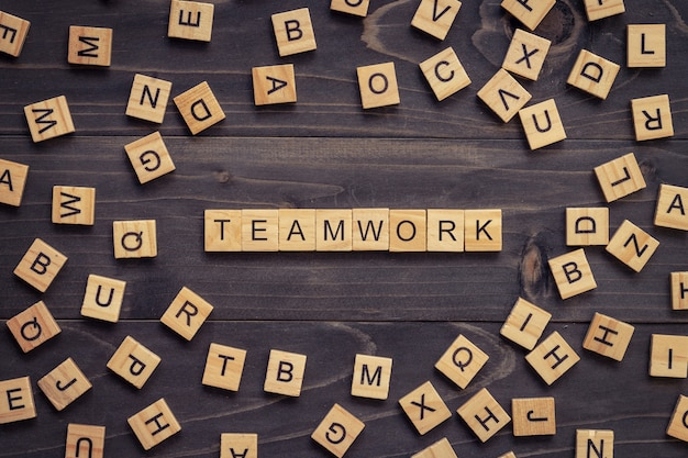 Teamwork wood text and wood block on table for business .