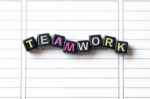 Teamwork word from blocks on clean page notebook close up.