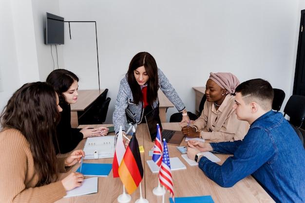 Командная работа. работа в многонациональной студенческой группе. учитель изучает иностранные языки вместе в классе.