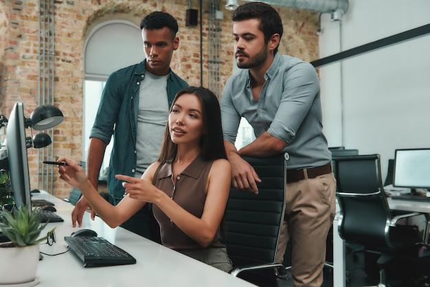 컴퓨터 모니터를 가리키고 보고서에 대해 토론하는 팀워크 젊은 아시아 여성