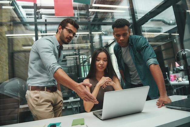 컴퓨터 모니터를 가리키고 두 사람과 프로젝트에 대해 토론하는 팀워크 젊은 잘생긴 남자