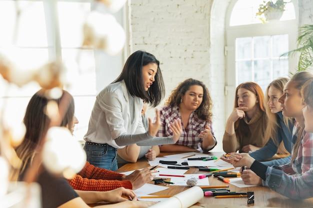 チームワーク。オフィスで女性の権利と平等について話し合う若者たち。白人のビジネスウーマンやサラリーマンは、職場の問題、男性のプレッシャー、ハラスメントについて話し合っています。