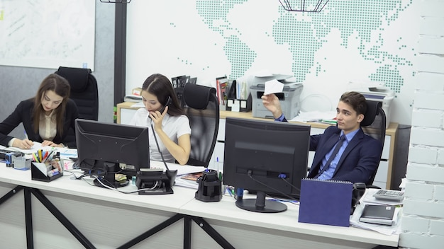 チームワーク。若いポジティブな女性従業員は、紙飛行機で遊んで休暇を夢見ている怠惰な男性マネージャーの隣で電話で顧客と話すことによって働きます