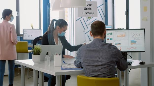 事業会社のオフィスのテーブルデスクに座っているコンピューターを使用してマーケティングプロジェクトで働いている間、フェイスマスクを着用しているチームワーカー。 covid19による感染を避けるために社会的距離を保つ同僚