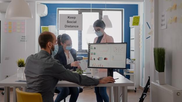 Сотрудники в защитных медицинских масках, работающие над маркетинговым проектом, анализируют отчеты, сохраняя при этом социальное дистанцирование в новом обычном офисе во время глобальной пандемии covid19