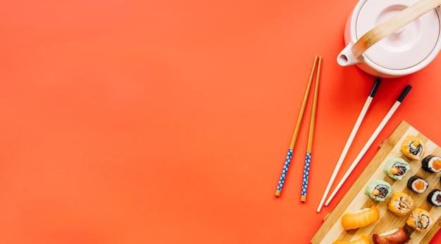 Чайник и палочки для еды возле суши