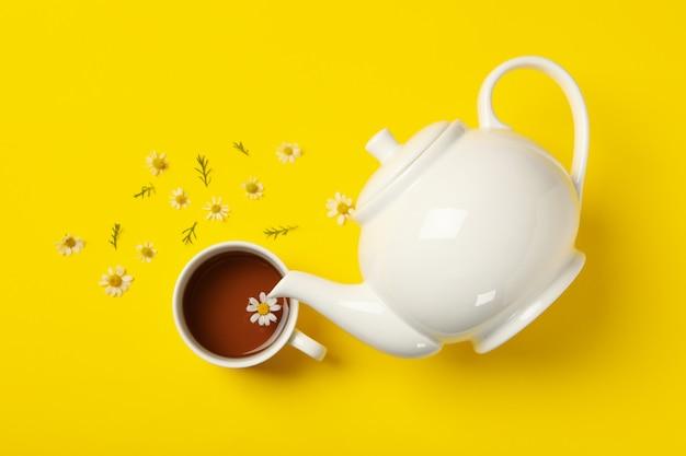 ティーポットとカモミールティーのカップに黄色の背景、トップビュー