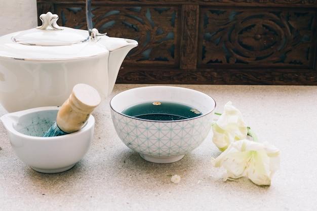 Чайник и чашка с синим чаем