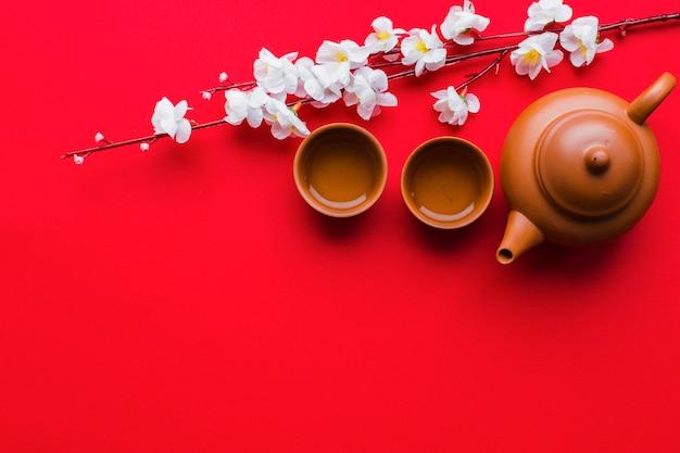 Чайник и чашки возле вишневой ветви