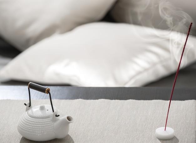Чайник и благовонная палочка на столе в уютном лаундже для отдыха