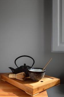 Чайник и чайный сервиз на деревянном подносе