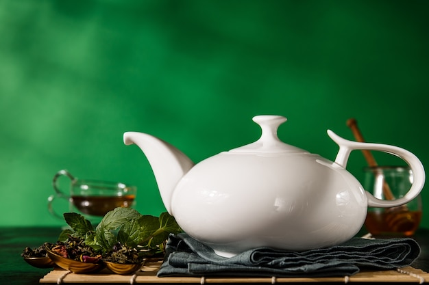 Teapot in arrangement with aromatic herbs