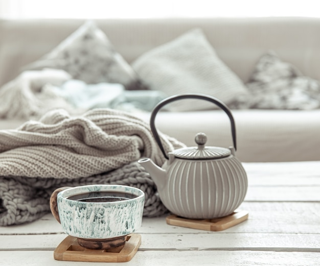 A teapot and a beautiful ceramic cup in a hygge style living room