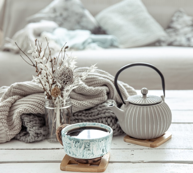 A teapot and a beautiful ceramic cup with decor details in a hygge style living room